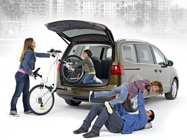 Семья возле автомобиля с велосипедом