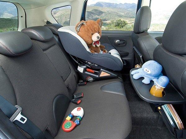 Задние сидения автомобиля и медведь в автокресле