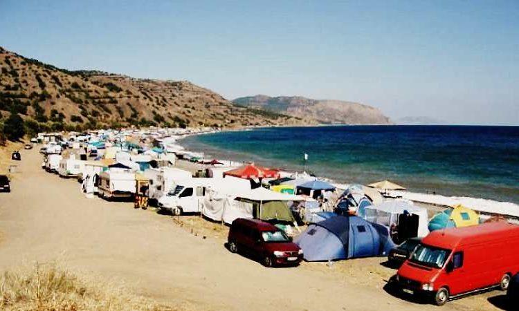 Палатки и автомобили на берегу моря