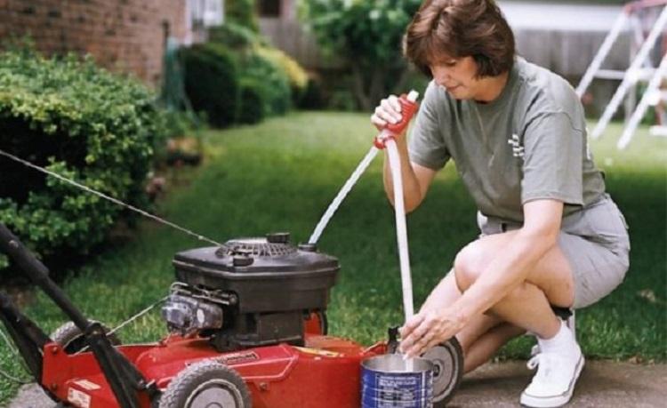 Женщина заправляетг газонокосилку