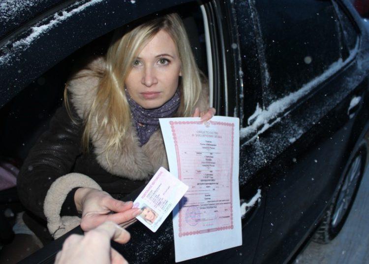 Девушка за рулем показывает права и страховку