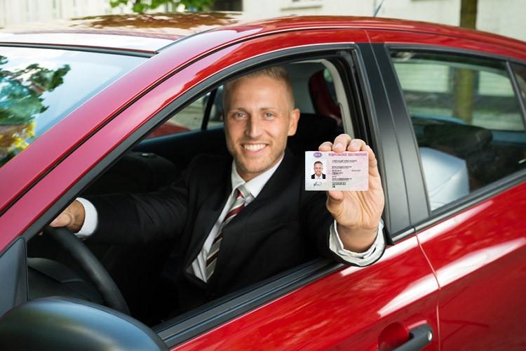 Мучжина за рулем показывает удостоверение