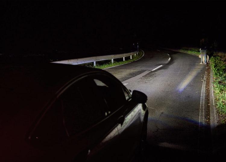 Человек на дороге под светом фар
