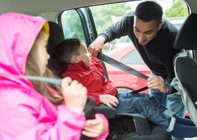 Мужчина пристегивает детей ремнями безопасности